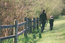 Mother and son walking in the grass next to fence rails.