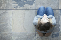 Aerial view of a woman sitting on her knees on tile in prayer.