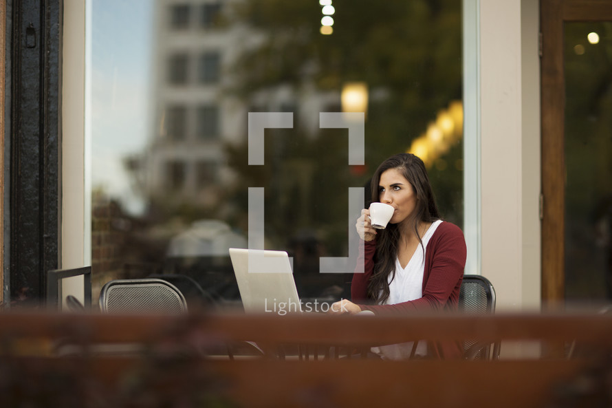 a young woman sitting outdoors at a table with a laptop sipping coffee.