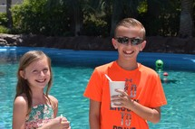 smiling children enjoying a summer day poolside with snow cones