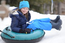 a girl tubing in the snow