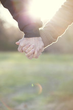 Mature couple holding hands in sunlight.
