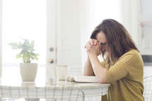 a woman praying over an open Bible sitting at a kitchen table