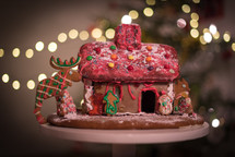 homemade gingerbread house and bokeh Christmas tree lights