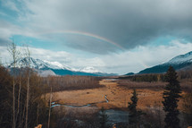 rainbow over snow capped mountains