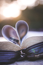 wedding bands in the pages of a Bible folded into the shape of a heart