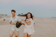 a playful couple running on a beach