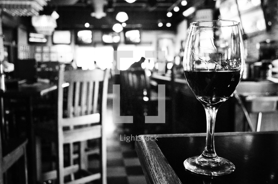 Glass of wine on corner of a bar.