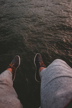 feet hanging over water