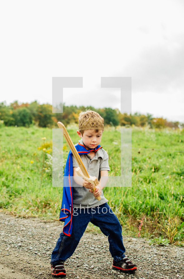 a boy in a cape holding a wooden sword