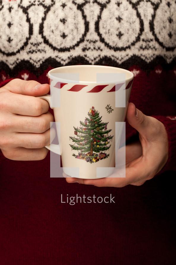 holding a Christmas mug