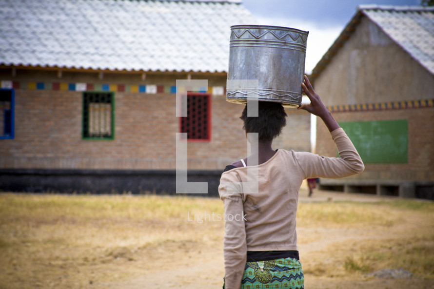 Woman carrying a metal bowl on her head