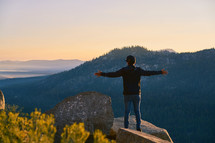 a man standing with open arms on a mountaintop looking out at the view