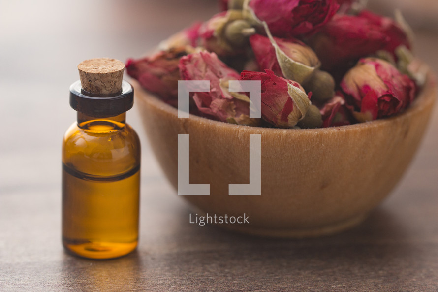 glass essential oil bottle and dried roses