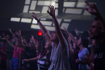 youth with raised hands in an audience