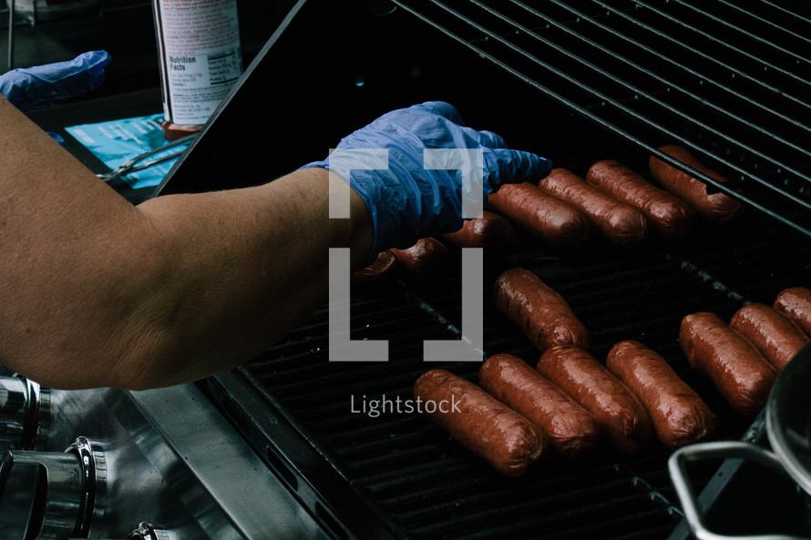 a man cooking sausage on a grill
