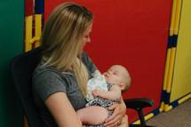 nursery room attendant cradling a baby