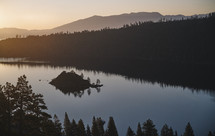 A lake right at the beginning of sunrise with mountains and trees in background