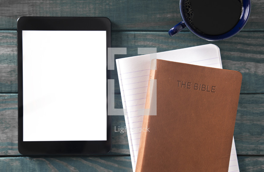 tablet, Bible, notebook, and coffee cup on a green wood background