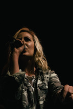 teen singing into a microphone