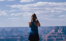 a woman standing at the edge of a cliff taking a picture with a cellphone camera