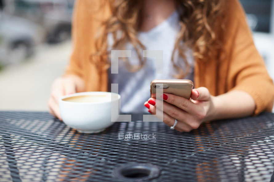 a woman sitting at an outdoor table drinking coffee and looking at her cellphone