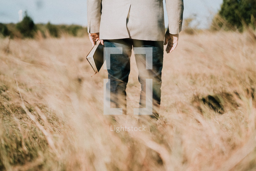 a man standing in a field holding a Bible at his side