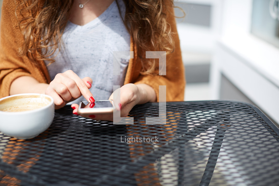 a woman sitting at an outdoor table and texting