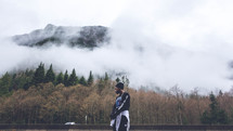 man standing in front of a view of fog over a mountain forest
