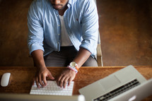 An African American man sitting at a desk typing on a computer
