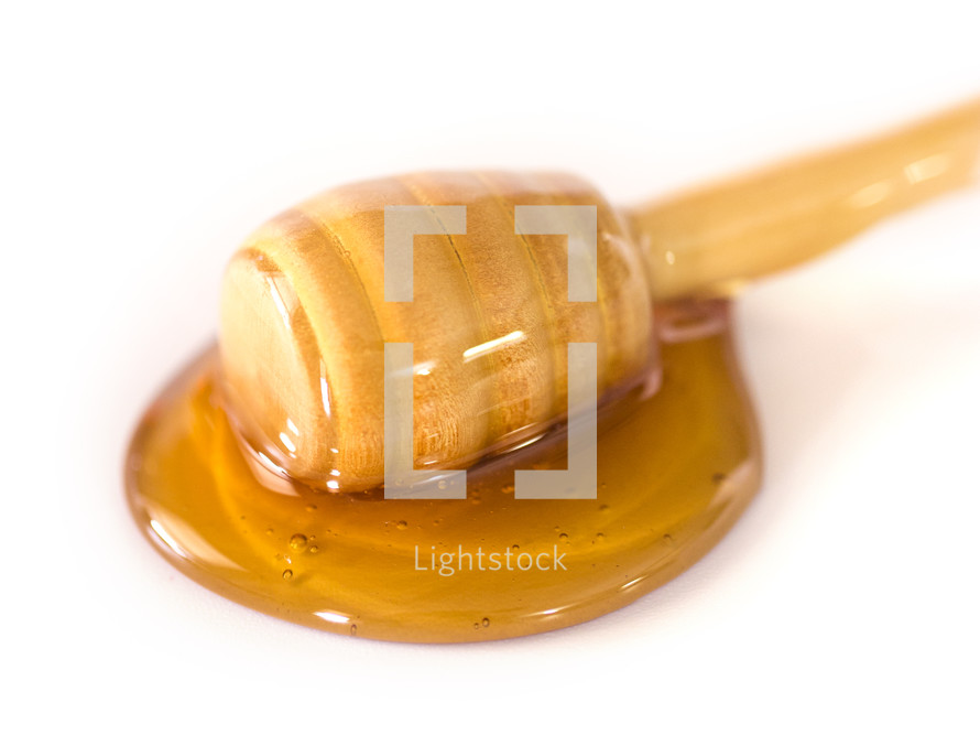 Honey with a Honeycomb Spoon on a White Background
