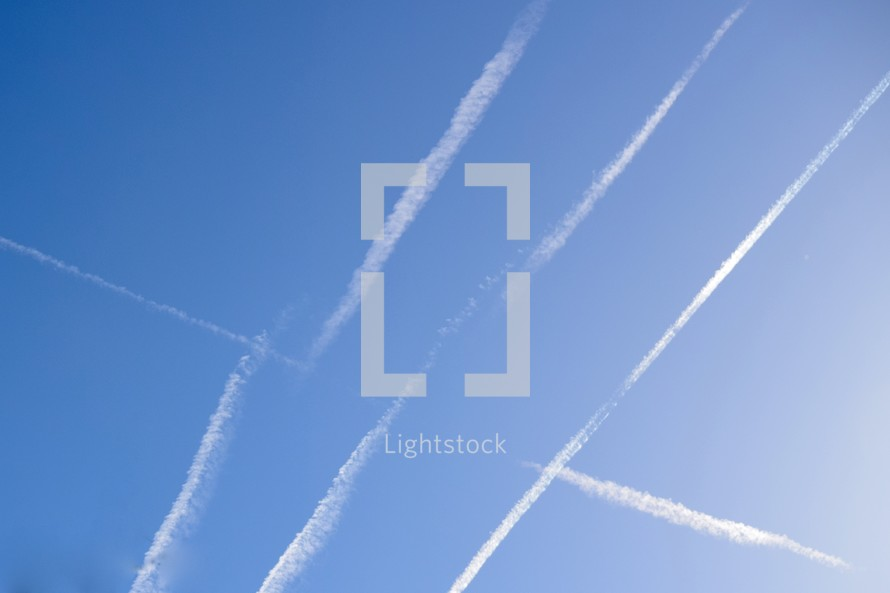 many plane contrails in the sky
