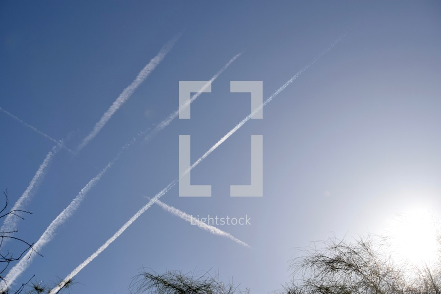 plane contrails in a sky at sunset