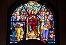 Stained glass window depicting the 12 disciples and Mary, mother of Jesus