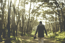 a man walking on a path in a forest carrying a Bible