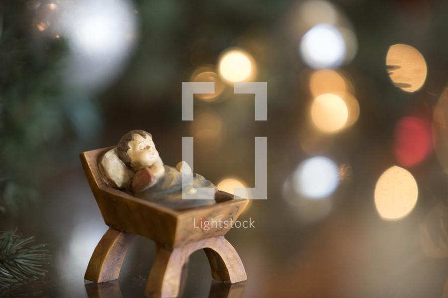 manger ornament and bokeh Christmas lights