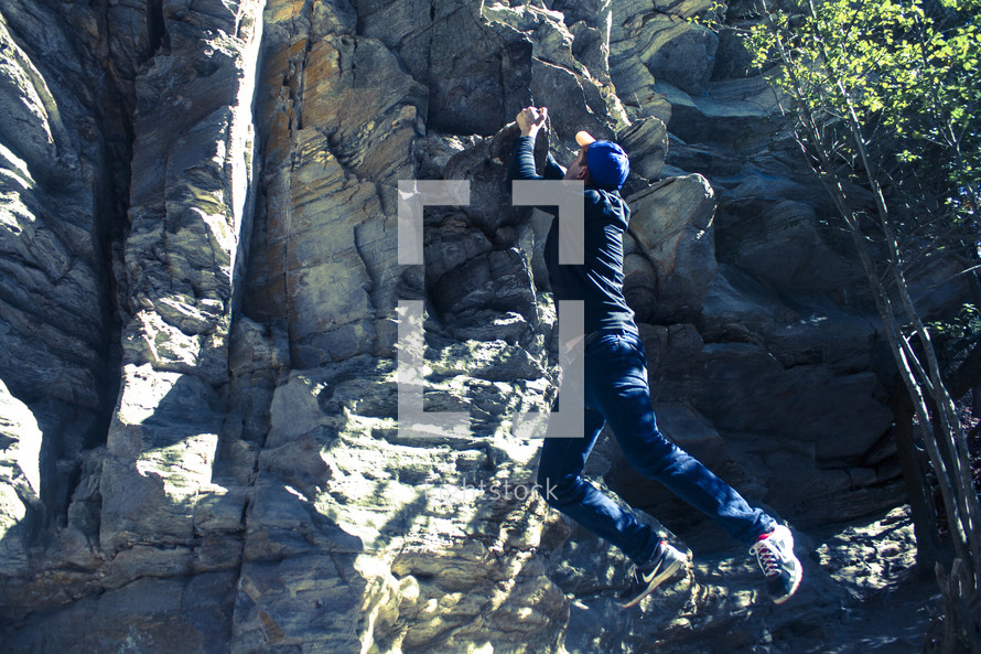 a man clinging to a rock wall