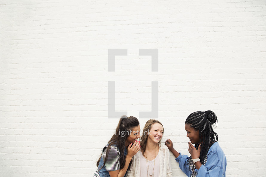 Three young women laughing together.