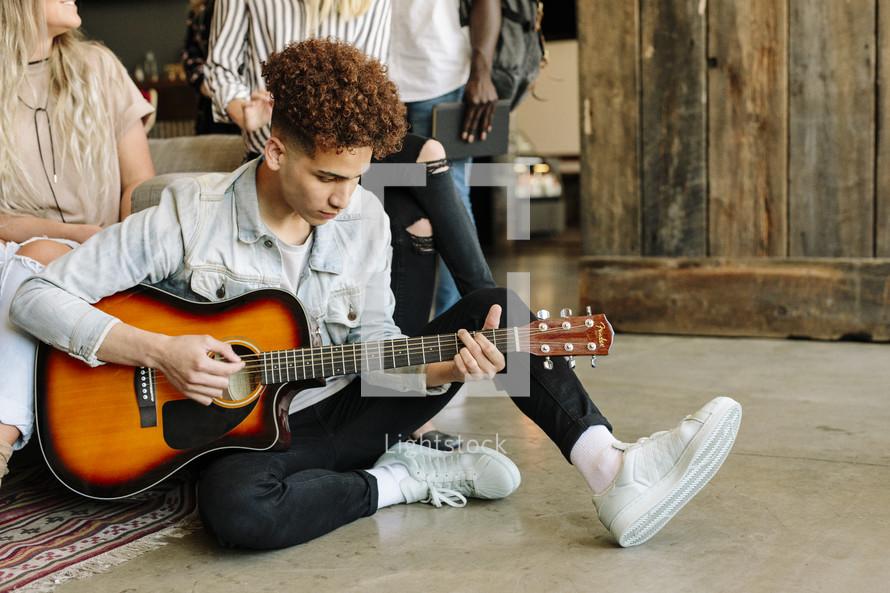 man playing a guitar at a Bible study