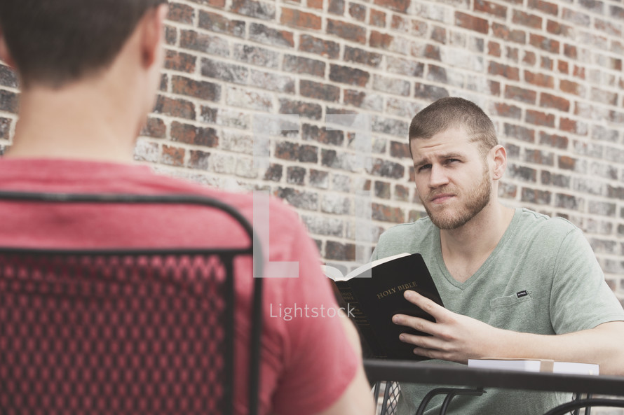 men reading a Bible during a Bible study outdoors