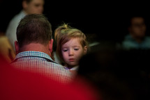 a father holding his toddler daughter at church
