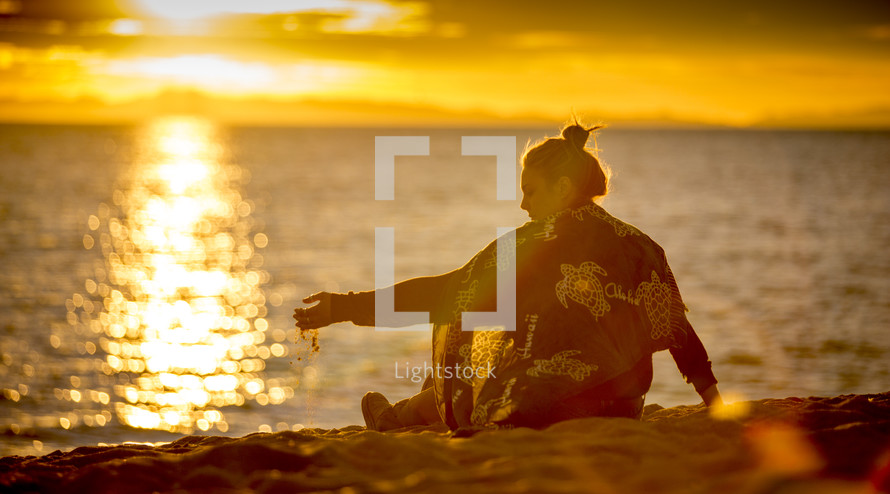 woman playing with sand on a beach
