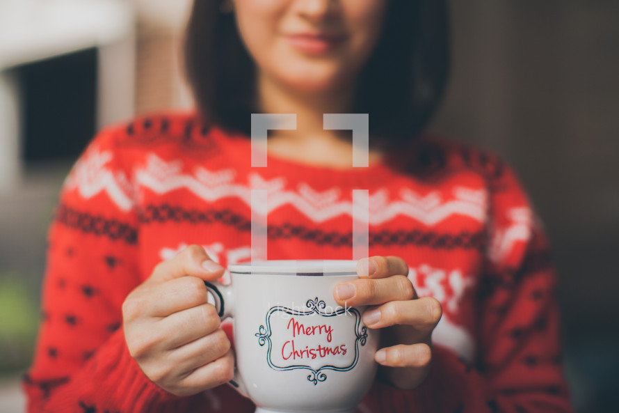 a woman holding a Merry Christmas coffee cup