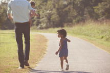 father and daughters walking down a path