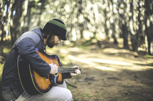 a man playing a guitar in a forest