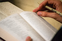 person reading a Bible and taking notes