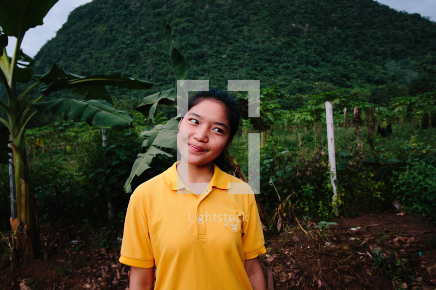 a smiling young woman in a clearing in the jungle