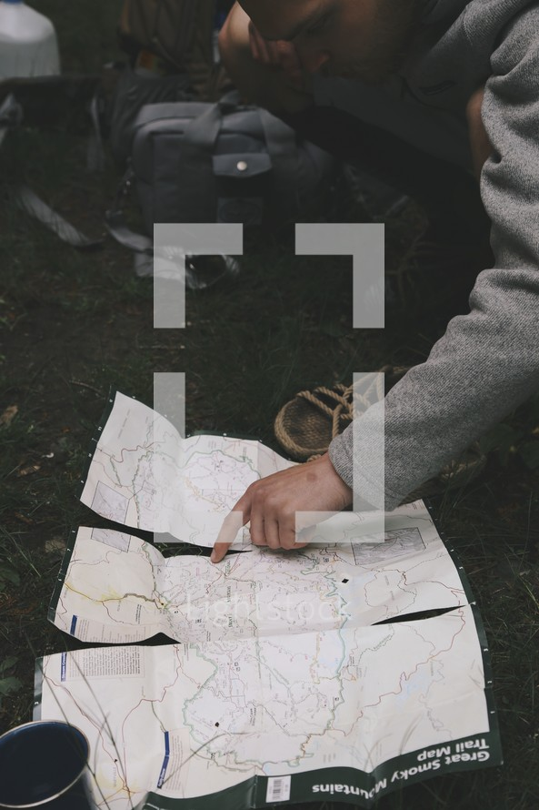 a man pointing to a trail map