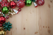 Christmas wrapping, bows, ornaments and gifts om a wood board.