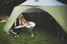 A family setting up a tent in the backyard.